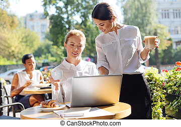 Pleasant woman looking at her colleagues laptop in cafe -...