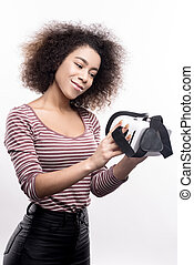 Pleasant woman looking at her new VR headset with love