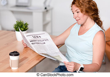 Pleasant woman reading newspaper