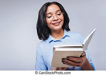 Pleasant woman reading notes in her notebook