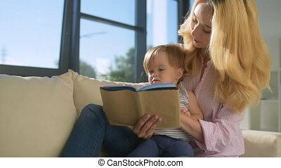 Pleasant woman reading to the child at home - Calm down, my...