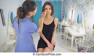 Pleasant woman stylist, working with mascara. Her client, a...