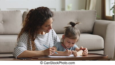 Pleasant woman teacher drawing pictures in album with little girl.