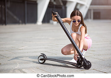 Pleasant woman using scooter