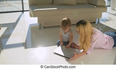 Pleasant woman with a cute child at home