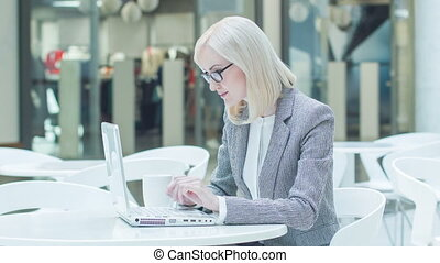 Pleasant woman working on laptop and drinking coffee. -...