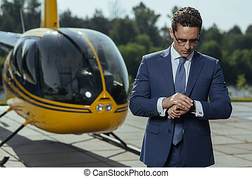 Pleasant young CEO checking time before helicopter ride