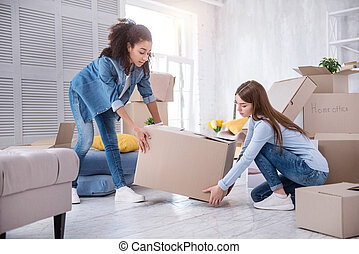 Pleasant young girls lifting up heavy box together