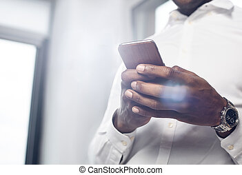 Pleasant young man is using smartphone