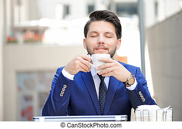 Pleasant young man sitting in cafe - Sumptuous aroma....
