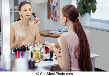 Pleasant young woman being ready to go out