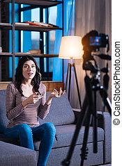 Pleasant young woman recording a video