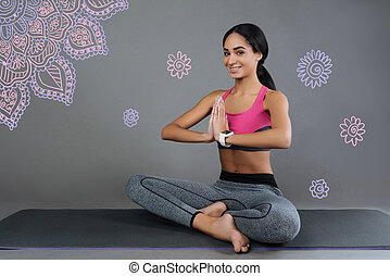 Pleasant young woman smiling while doing yoga exercises