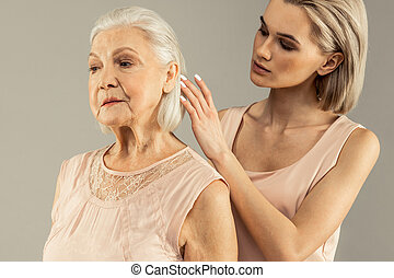Pleasant young woman touching her mothers hair