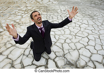 Photo of helpless businessman standing on dry ground and raising his arms upwards