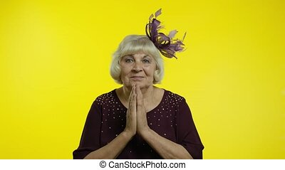 Please, I am begging. Positive senior old blond woman appealing to camera, keeping prayer gesture and asking help, apologize. Elderly stylish lady grandma on yellow background in studio. 6k footage