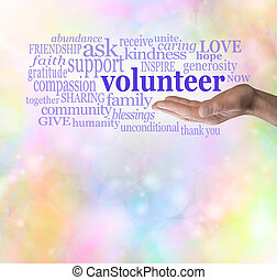Male hand palm up with the word 'volunteer' floating above surrounded by relevant words on a rainbow colored bokeh background