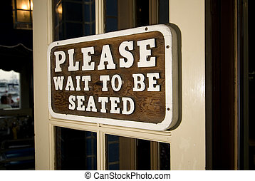 Please Wait to be Seated sign at a restaurant or club.