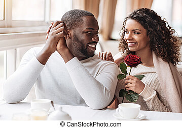 Pleased African American couple having the date in the cafe