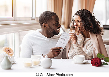 Pleased African American woman getting a ticket from her boyfriend