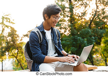 Pleased asian male student in eyeglasses using laptop computer
