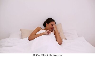 Pleased attractive woman waking up peacefully in her bed