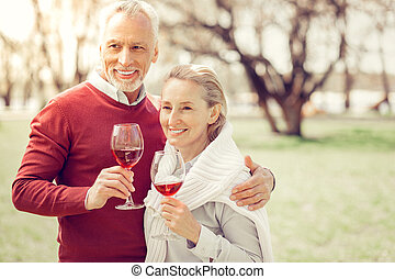 Pleased bearded man standing close to his wife