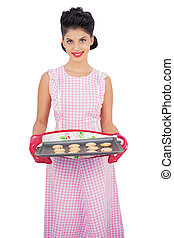 Pleased black hair model holding a baking tray of cookies on...