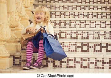 Pleased blonde girl 3 years old with shopping