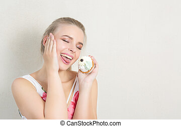 Pleased blonde girl having fun with a sweet dessert with butter cream. Space for text
