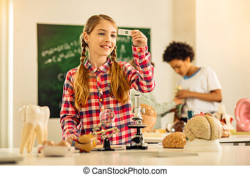 Pleased blonde girl studying with her classmates