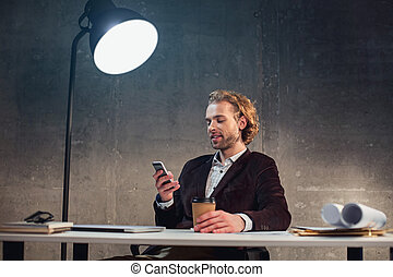 Pleased businessman using phone at table