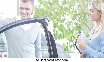 Pleased customer sitting inside his brand new car.