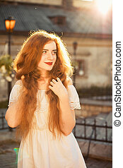 Pleased ginger young model with naked long wavy hair posing in sun glare at sunset