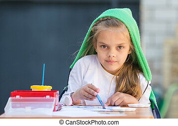 Pleased girl draws paints at the table and looked at the frame