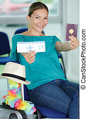 pleased lady with passport with boarding pass in hand