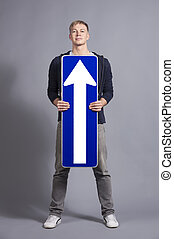 Pleased man holding direction arrow sign pointing up.