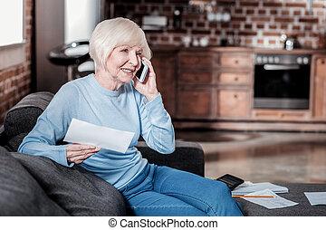 Pleased mature woman having positive conversation
