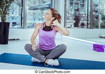 Pleased mature woman massaging neck in gym