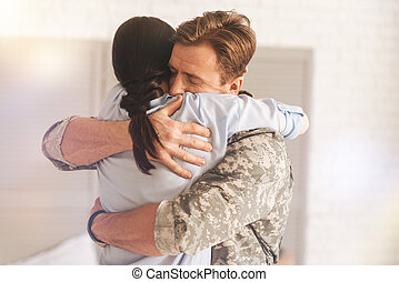Pleased military man embracing his wife