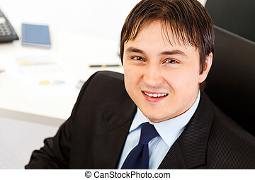 Pleased modern business man sitting at office desk