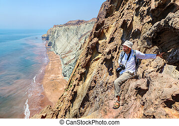 Pleased nature photographer is sitting on the edge of cliff.