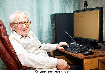 smiling pleased old man sitting near computer - he is working