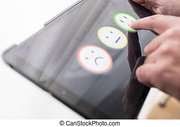 pleased person giving positive feedback by touching smiley face on digital tablet touchscreen