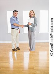 Pleased realtor and buyer shaking hands - Pleased blonde...