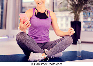 Pleased sportswoman sitting in yoga pose on mat
