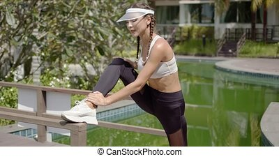 Cheerful slim lady in sportswear stretching leg near railing of bridge near calm pool during outdoor training on sunny day on tropical resort