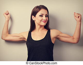 Pleased strong young woman showing muscle biceps with smiling. Toned closeup portrait