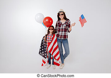 Pleased stylish mother and daughter celebrating national holiday together