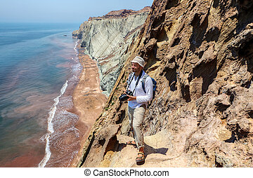Pleased traveller with camera stands on the edge of a cliff.